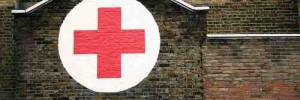 A red cross painted in a white circle on the side of a house in Dalston