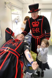 Blood transfusion beneficiary, Hannah Farrands, with Yeoman Warder Robin Fuller as he donates blood at the Tower of London.