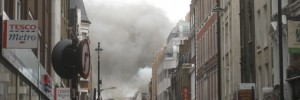 Smoke billows from the upper storey of buildings on Dean Street.
